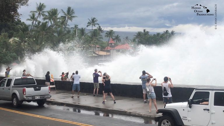 Incoming waves tower over bystanders in Kona, Hawaii, U.S. August 23, 2018 Credit: Ryan Leinback