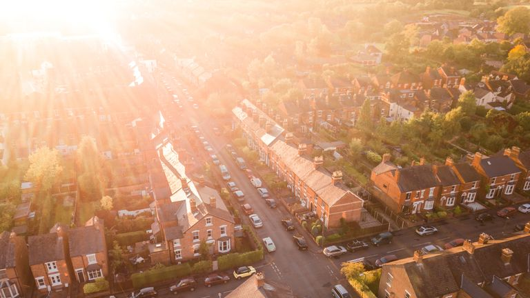 Aerial view of the sun setting over a cross roads in a traditional UK suburb - Stock image