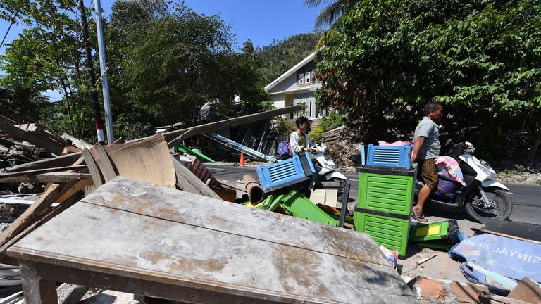 People salvage belongings from a destroyed building in Pemenang in northern Lombok island