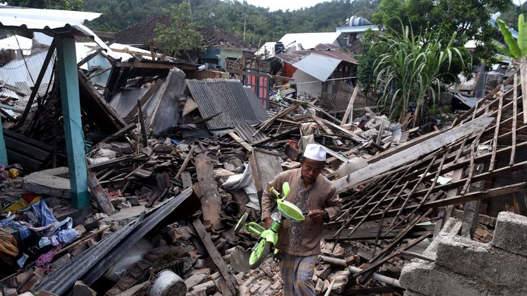 A man carries a small bicycle through the ruins of houses damaged by an earthquake in West Lombok, Indonesia, August 6, 2018 in this photo taken by Antara Foto. Antara Foto/Zabur Karuru / via REUTERS ATTENTION EDITORS - THIS IMAGE WAS PROVIDED BY A THIRD PARTY. MANDATORY CREDIT. INDONESIA OUT.
