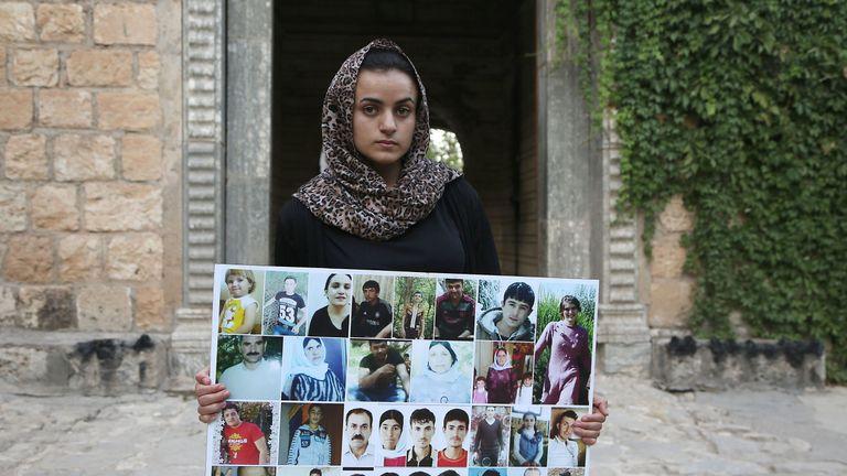 Ms Hami holding a portrait of sex slaves from her village of Kocho near Sinjar