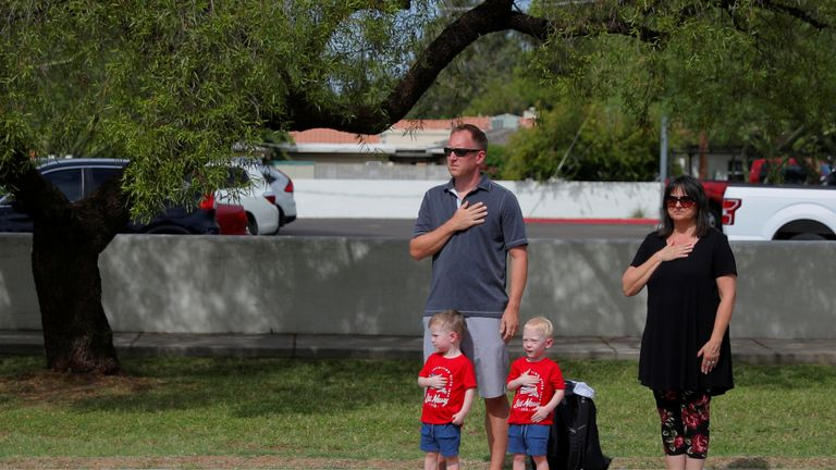 A family pays their respects as the motorcade passes