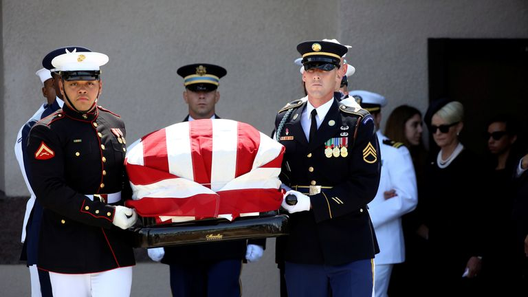 The McCain family follows as military bearers carry the senator's casket out of the church in Phoenix