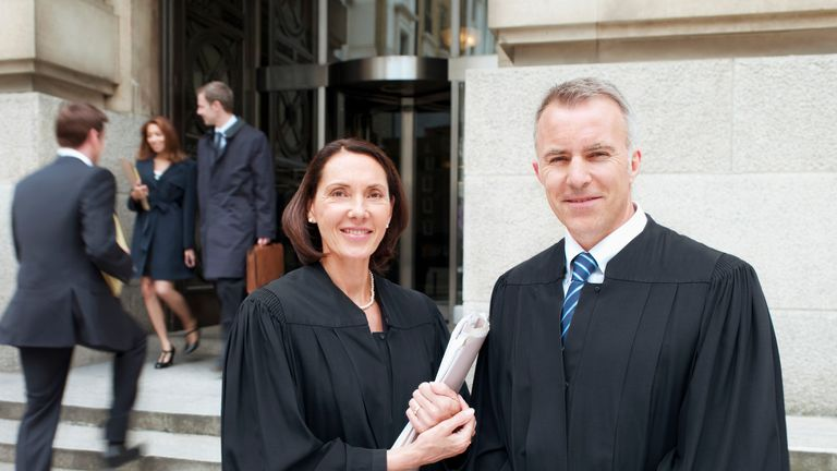Smiling judges in robes standing outside courthouse - Stock image