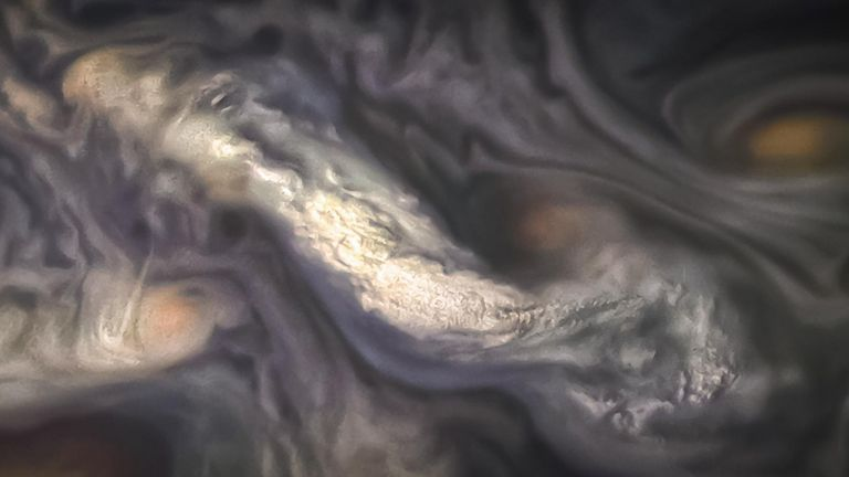 This image captures a high-altitude cloud formation surrounded by swirling patterns in the atmosphere of Jupiter's North North Temperate Belt region. The North North Temperate Belt is one of Jupiter's many colorful, swirling cloud bands. Scientists have wondered for decades how deep these bands extend. Gravity measurements collected by Juno during its close flybys discovered that these bands of flowing atmosphere actually penetrate deep into the planet, to a depth of about 1,900 miles (3,000 kil
