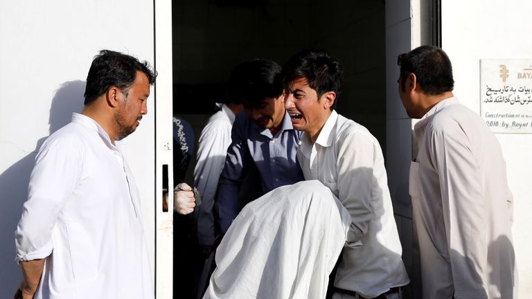 An Afghan man holds the body of his relative killed in the Kabul attack