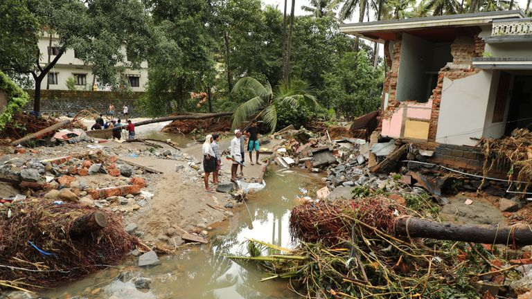 Indian residents look at houses destroyed by flood waters at Kannappankundu in Kozhikode, in the Indian state of Kerala