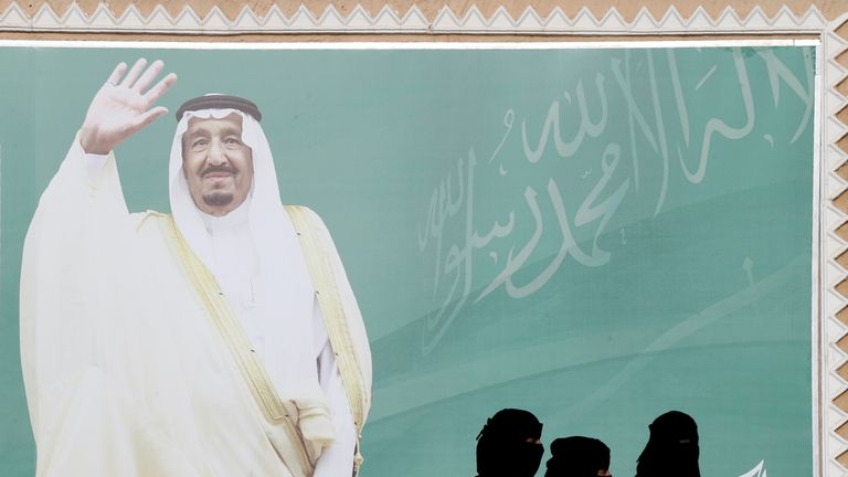 Women walk past a poster of Saudi Arabia's King Salman bin Abdulaziz Al Saud