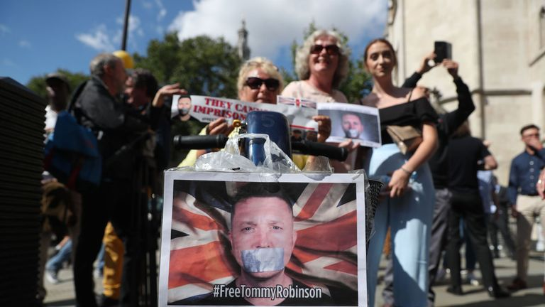 Supporters of jailed English Defence League (EDL) founder Tommy Robinson, real name Stephen Yaxley-Lennon, react outside the Royal Courts of Justice in London on August 1, 2018