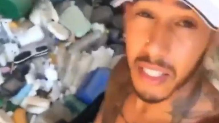 Lewis Hamilton collects plastic waste from a beach while on holiday