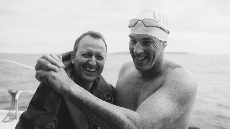 Lewis and friend David Becker celebrate the fast swim
