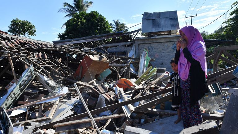 TOPSHOT - A woman and boy watch as men clear the wreckage of houses damaged by an earthquake in Menggala, North Lombok on August 8, 2018, three days after the earthquake struck the area. - The shallow 6.9-magnitude quake destroyed thousands of buildings and triggered panic among tourists and locals on Lombok on August 5, just a week after a tremor had surged through the holiday island and killed 17.