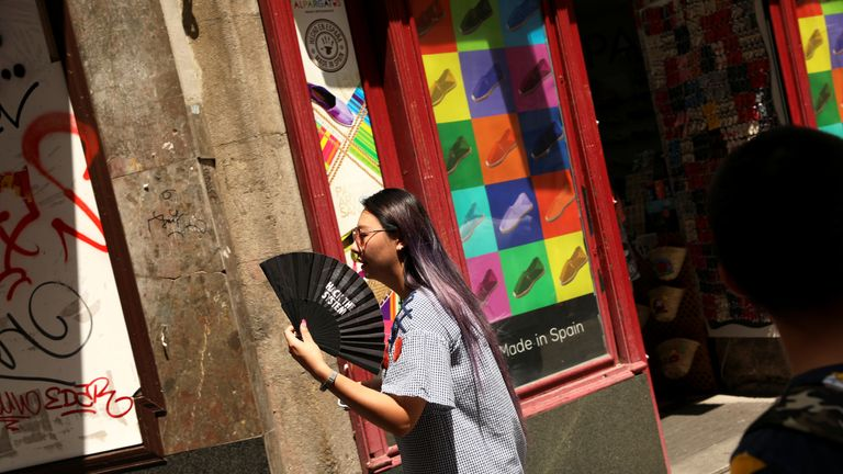 A woman in Madrid fans herself as temperatures soar throughout the country