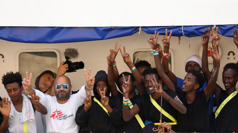 Crew and migrants celebrate as they dock in Malta
