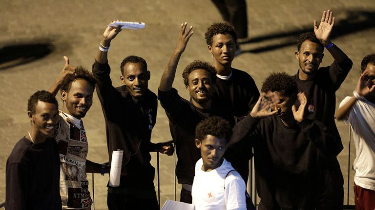 Migrants wave after disembarking from Italian coast guard vessel Diciotti at the port of Catania