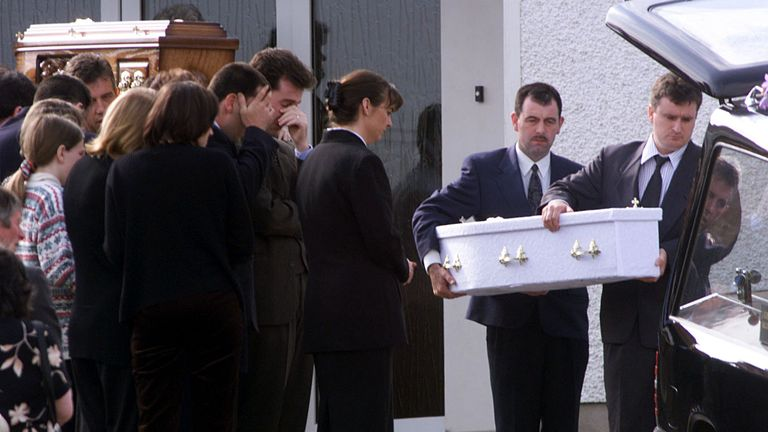 Michael Monaghan (2nd L) covers his eyes as the coffin carrying 18-month-old baby daughter Maura, and wife Avril (unseen) leave his house