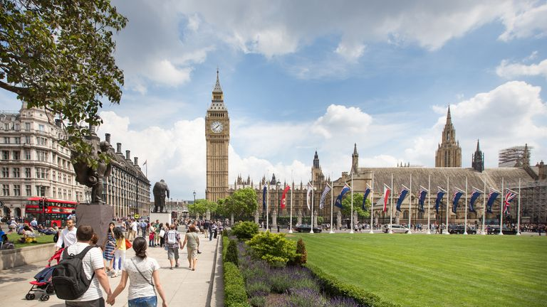 Tourists flocking around Parliament Square in Westminster, London on a sunny summers day