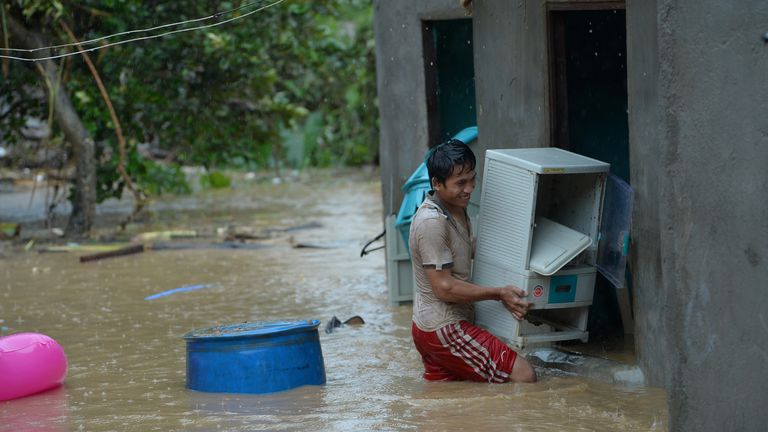 A resident carries a plastic cabinet inside their flooded house after a heavy downpour in the Philippines