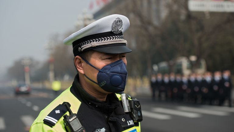 A police officer Beijing protects wears a mask to avoid breathing in polluted air