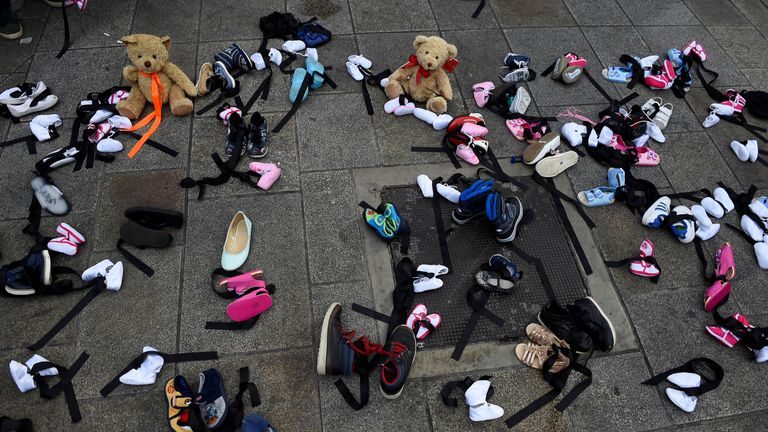 Children's shoes and toys are scattered on a street in Dublin as part of a protest during Pope Francis' visit