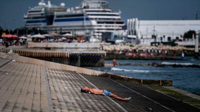 A man sunbathes at Ribeira das Naus in Lisbon on August 3, 2018. - Two men died from heatstroke in Spain as Europe sweltered in a record heatwave today, with temperatures hitting a scorching 45 degrees Celsius in some areas and meteorologists saying only scant relief is in sight in the coming days. The highest temperature ever recorded in Europe was 48 degrees in Athens in 1977, closely followed by 47.3 in Amareleja, Portugal in 2003 as well as in Montoro, Spain last year. (Photo by PATRICIA DE