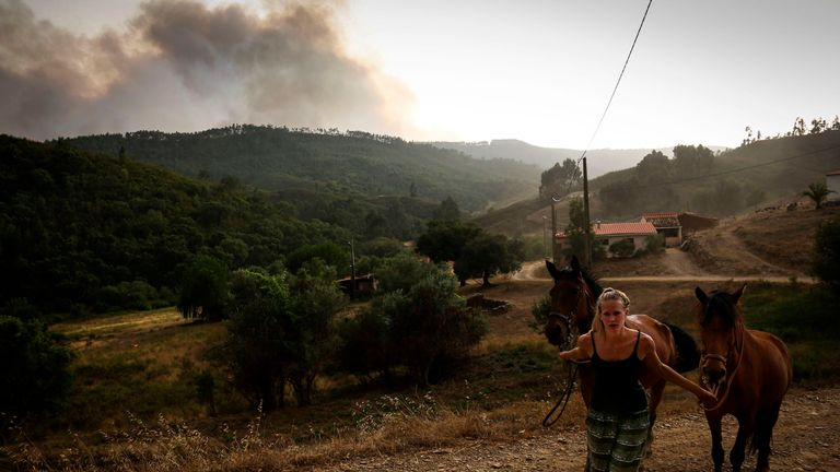 A woman pulls two horses as smoke columns rise due to a wildfire close to Monchique in the Portuguese Algarve, on August 4, 2018. - A village in a tourist area in southern Portugal was evacuated as more than 400 firefighters tackled a forest fire, emergency services said. With Europe still on high alert during a record-breaking and deadly heatwave, Portugal has seen the mercury reach almost 46 degrees Celcius -- with more hot days to come. (Photo by CARLOS COSTA / AFP) (Photo credit should read