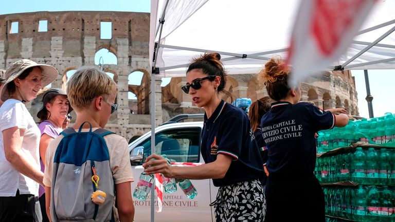 Members of the Italian Civil Protection (Protezione Civile) distribute water bottles to people and tourists in front of the Ancient Colosseum, in central Rome