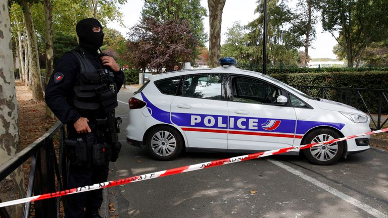 French police secure a street after a man killed two people and injured one other in a knife attack in Trappes