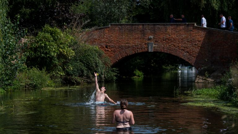 A couple play catch in the River Stour in Fordwich, Kent, as a second heatwave continues in the UK