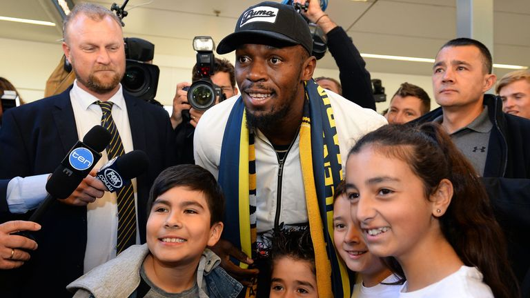 Usain Bolt poses for pictures with fans upon arrival at Sydney international airport
