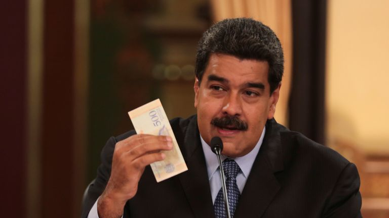 Venezuela's President Nicolas Maduro holds a bank note from the new currency Bolivar Soberano (Sovereign Bolivar)