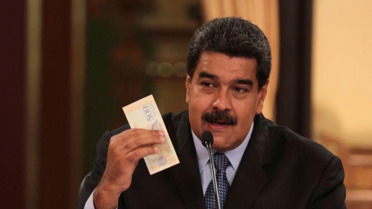 Venezuela's President Nicolas Maduro holds a bank note from the new currency Bolivar Soberano (Sovereign Bolivar)