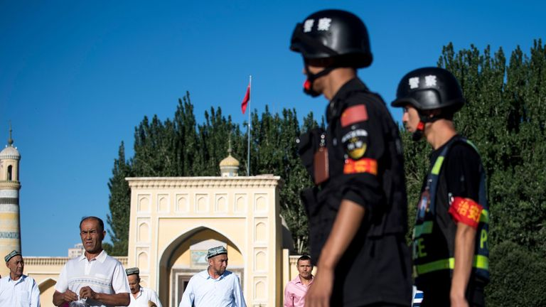 Police patrolling as Muslims leave the Id Kah Mosque after the morning prayer on Eid al-Fitr in the old town of Kashgar in China's Xinjiang region