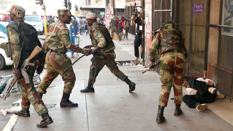 A soldier appears to attack a man on the streets of Harare