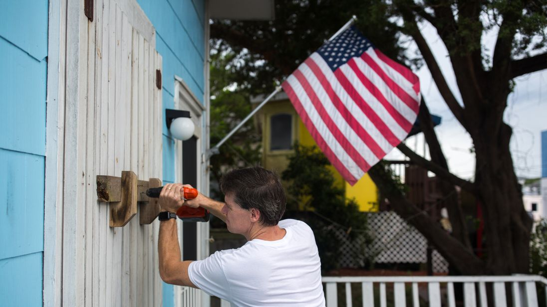 A man helps board up Aussie Island surf shop on September 11, 2018 in Wrightsville, North Carolina in anticipation of Hurricane Florence's high storm surge