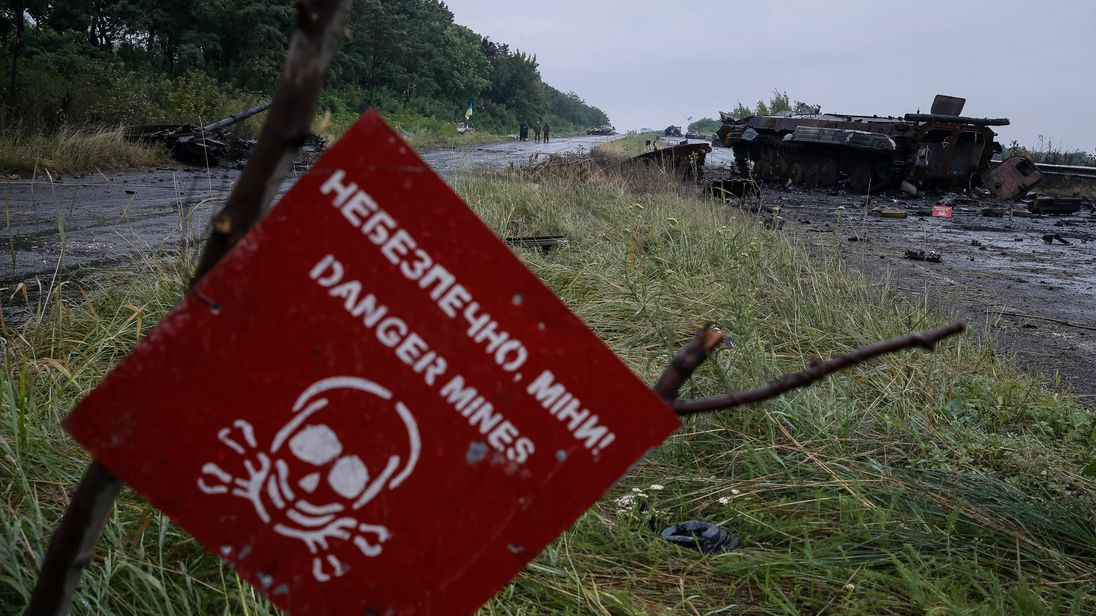 A destroyed military vehicle is seen near a landmine warning sign just outside the eastern Ukrainian town of Slaviansk July 7, 2014