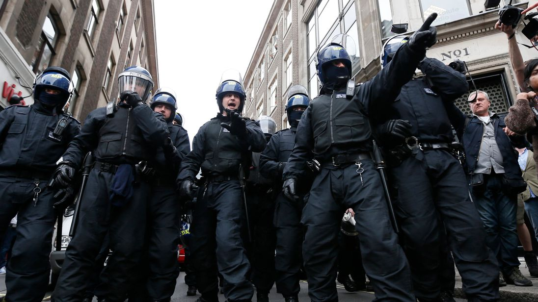 Police officers form a cordon after raiding a building used as a base for demonstrators protesting against the upcoming G8 summit in central London June 11, 2013
