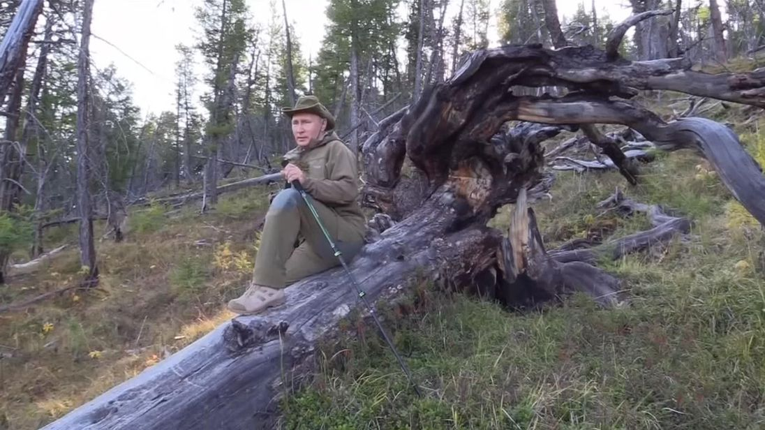 Vladimir Putin sits on a tree trunk while on holiday in Siberia