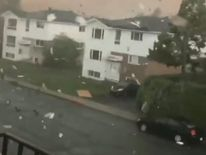 Tornado sweeps through Quebec as debris fly over sky.