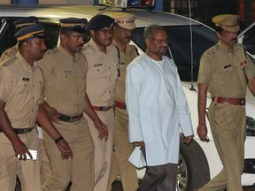 Bishop Franco Mulakkal (second right) is escorted by police outside a crime branch office on the outskirts of Kochi