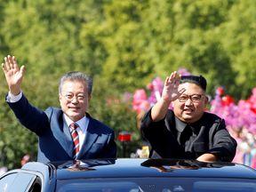 South Korean President Moon Jae-in and North Korean leader Kim Jong Un wave during a car parade in Pyongyang, North Korea