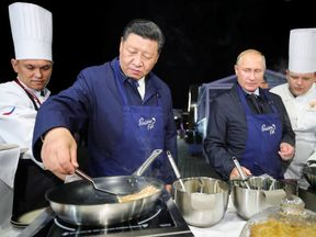 Russian President Vladimir Putin and Chinese President Xi Jinping make pancakes during a visit to the Far East Street exhibition on the sidelines of the Eastern Economic Forum in Vladivostok, Russia September 11, 2018.
