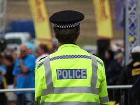 British police man backwards to the camera - Stock image