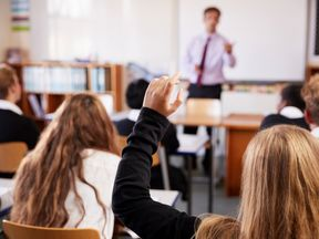 Female Student Raising Hand To Ask Question In Classroom - Stock image