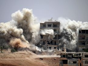 Smoke rises following a reported air strike on a rebel-held area in Daraa in June 2017