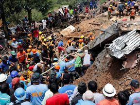 Rescuers search for people trapped in a landslide caused by Typhoon Mangkhut at a small-scale mining camp in Itogon, Benguet, in the Philippines