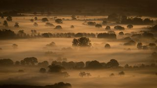 Early morning mist lingers in fields as the autumn sun rises over the Somerset Levels as viewed from Glastonbury Tor near Glastonbury on September 22, 2017