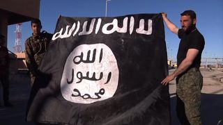 Two rebel soldiers hold up an Islamic State flag after the liberation of the town of al Shaddidi