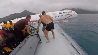 US Navy sailors rescuing passengers after plane crashes into water in Micronesia.