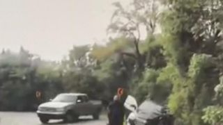 Woman is dragged out of path of oncoming vehicle